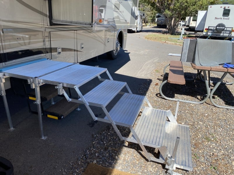 Side view of folding deck and stairs set up against a motorhome