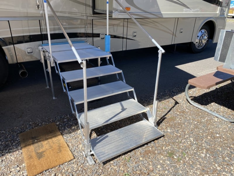 Folding deck and stairs set up against a motorhome